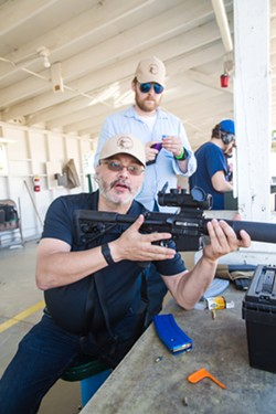SAFETY LESSON Safety instructor and The Liberal Gun Club Executive Director Ed Gardner gives a lesson on how to properly and safely handle this variant of the AR-15, which was modified to shoot .22 caliber bullets and is 10 percent as powerful as a regular AR-15. - PHOTO BY JAYSON MELLOM