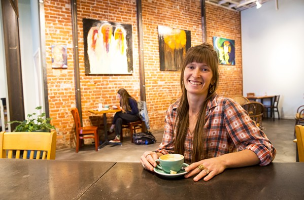 COFFEE SHOP CURATOR Manager and curator for Ascendo Coffee Jenna Madama sips on a coffee in front of the café's current display of paintings by artist David Zweifel. - PHOTO BY JAYSON MELLOM