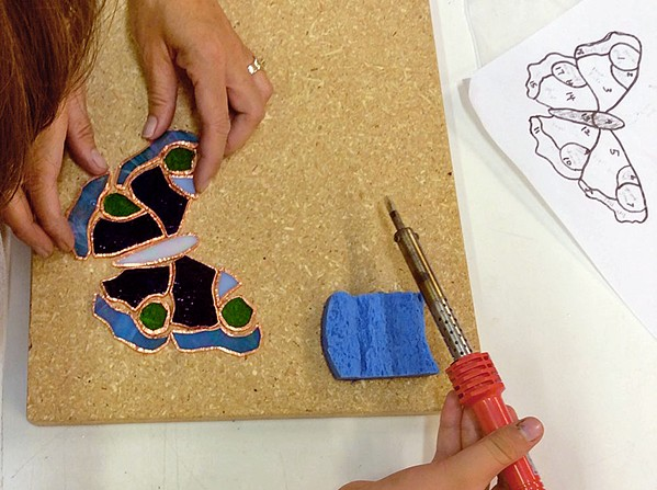 TAKE FLIGHT A class participant at Glasshead Studio makes a mosaic butterfly. - PHOTO COURTESY OF LISA RENÉE FALK