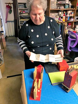 SURPRISE INSIDE Meryl Perloff shows one of her accordion-style books while standing in her home studio in San Luis Obispo. - PHOTO BY MALEA MARTIN