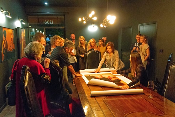 UNVEILING Carrie Graber shows guests prints of her work on the grand table of LXV winery's Library Room. - PHOTOS COURTESY OF ALEX LOPEZ