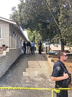 DEADLY FORCE SLO police officers and investigators stand around Regalia and Manford's driveway, minutes after one of their officers fired three rounds at a dog, which they say charged at him on Sept. 26. - PHOTO BY PETER JOHNSON