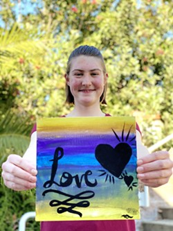 LOVE Aunica Todd, a student at Heartland Charter School, holds up artwork she created for Youth Art After Dark, an exhibit highlighting teen dating violence and healthy relationships. - PHOTO COURTESY OF ARTI KOTHARI ALLARD