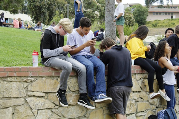 TTYL SLO High School students check their phones at lunch in 2019. The Paso Robles board of education is considering a new electronic device policy that would prohibit the use of cellphones, smart watches, and other mobile devices at all district sites during instructional time. - FILE PHOTO BY KASEY BUBNASH