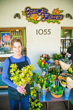 DOWNTOWN FLORA Open Air Flowers has brightened up Osos Street for years with its selection of buds and petals that spill out onto the sidewalk. Owner Leslie Weber holds up a collection of orchids from the display at the Best Flower Shop in the county. - PHOTO BY JAYSON MELLOM