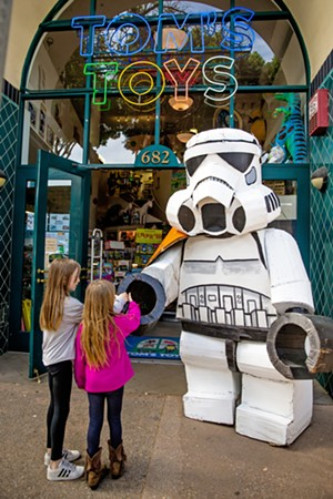 DARTH SIGHTING Charlotte Petit, 10, and Maddie Petit, 8, shake hands with the dark side at Tom's Toys, aka the Best Toy Store ever. - PHOTO BY JAYSON MELLOM