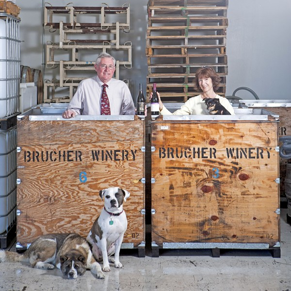 TEAM EFFORT :  Mike and Janis Schmidt own and operate the Brucher and Golden Bear wine company in Santa Maria, which help from Gracie (lying down), Pirate, and Dub (in Janis' arms). - PHOTO BY STEVE E. MILLER