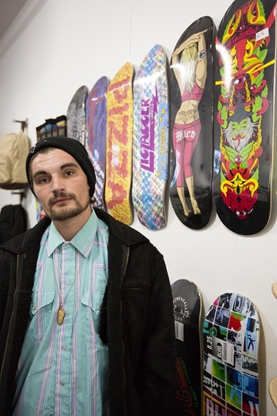 INSPECTAH DECK:  Jake Johnson stands in front of the many custom skateboards at PMA Retail Gallery, where he will be showing his art and neverbefore-seen music video. - PHOTO BY KAORI FUNAHASHI