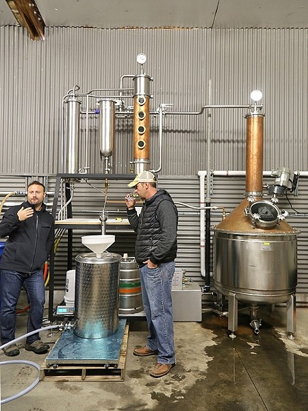 QUALITY CONTROL:  Stephen Kroener, left, talks about the intricacies of the distillation process as Joe Barton, right, takes a whiff of their distilled brandy. The two, who are both winemakers, make gin and whiskey at their aptly named distillery Krobar. - PHOTO BY DYLAN HONEA-BAUMANN