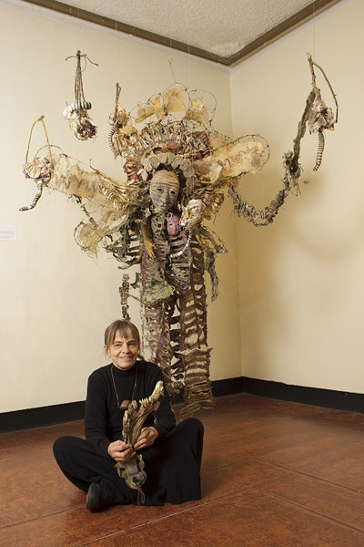 """GUARDIAN ANGEL? :  Performance artist and sculptor Sha Sha Higby sits at the feet of one of her dazzling creations. Higby's aesthetic was greatly influenced by a trip to Japan, where she discovered Noh, a 600-year-old tradition of dance theater that, she said, """"changed my whole life aspect."""" - PHOTOS BY STEVE E. MILLER"""