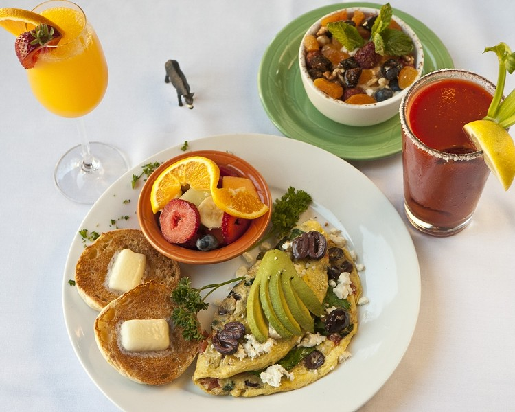 "GRECIAN DELIGHTS :  The Wild Donkey café is now serving Greek inspired breakfasts like this Greek omelet and Greek Island fruit and yogurt dish. Also pictured are a Bloody Mary and Mimosa. As the server Lane put it, ""I never have one drink with breakfast!"" - PHOTO BY STEVE E. MILLER"