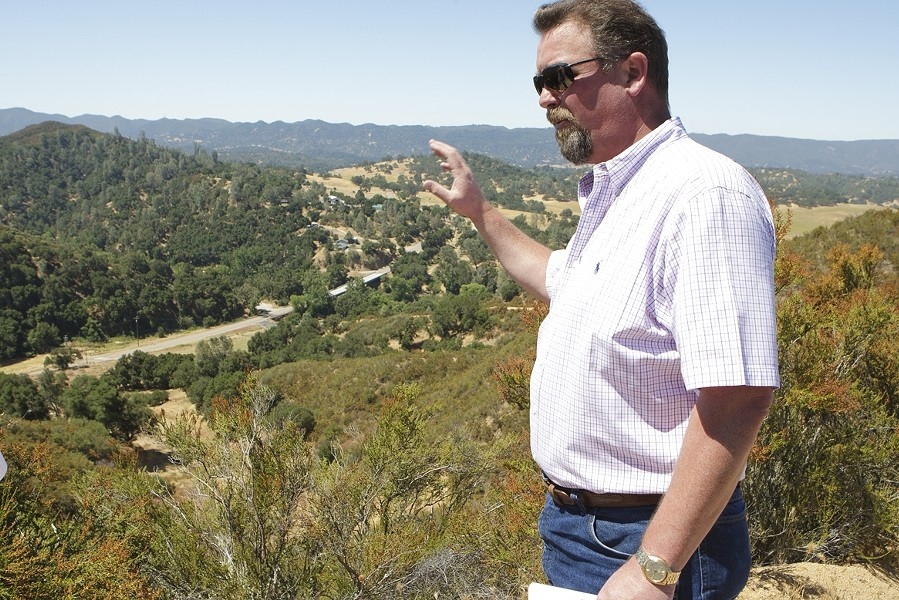 ROCK AND ITS ROLE :  Ken Johnston stands on a ridgeline that separates the main quarry from Highway 58 (seen in the distance). - PHOTO BY STEVE E. MILLER