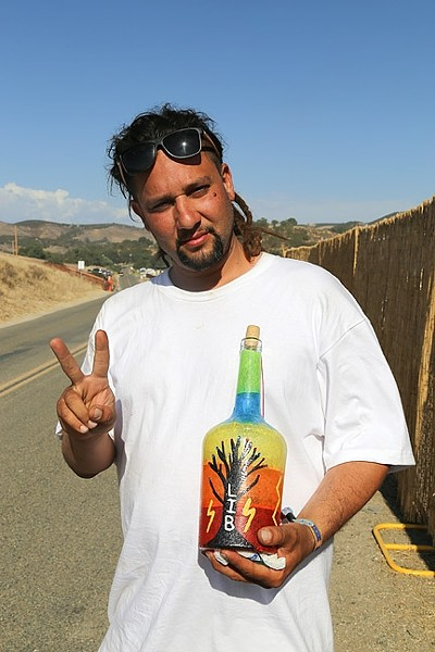 "LIGHTNING IN A GIFT :  Mike Dominguez holds up a hand-painted bottle given to him by a woman at LIB. Dominguez believes that LIB is part of the ""Hopi prophecy of us rebelling against what was created and trying to create something new for the future of our children, for the future of humans."" - PHOTO BY DYLAN HONEA-BAUMANN"