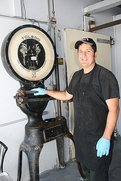 MEAT ACROSS THE AGES:  Rife with history, Arroyo Grande Meat Co. has been a full-service butcher shop since 1897. This scale was used to weigh meat back in the day and—if owner/butcher Henry Gonzalez (pictured) has his way—it will one day work again. - PHOTO BY HAYLEY THOMAS CAIN