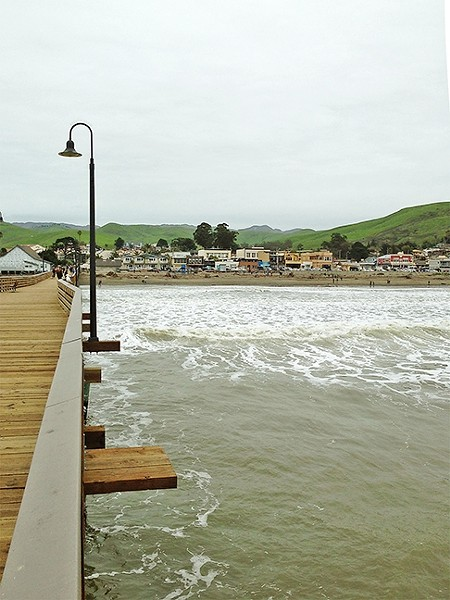 PIER-ING BACK:  The view from the end of the Cayucos pier back to shore was magnificent: bright green rolling hills and the funky beach town of Caycuos in the foreground. - PHOTO BY PETER JOHNSON