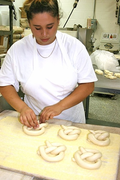 NO STEPS SKIPPED :  House of Bagels Central Coast bagelmaker Molly Bueno shapes the eatery's new pretzels. - PHOTO BY HAYLEY THOMAS