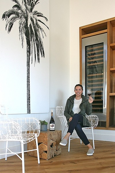 MEET ME UNDER THE PALM:  Biddle Ranch Vineyard General Manager Leigh Woolpert raises a glass of earthy pinot noir to the year ahead among the graphic palm tree décor, which adds a splash of quirk to the Edna Valley tasting room. - PHOTO BY HAYLEY THOMAS CAIN