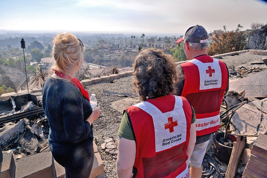 GONE Linda Allen stands with Red Cross volunteers as she looks at the remainder of her home in Ventura's Skyline neighborhood. - PHOTO BY DERMOT TATLOW COURTESY OF THE RED CROSS