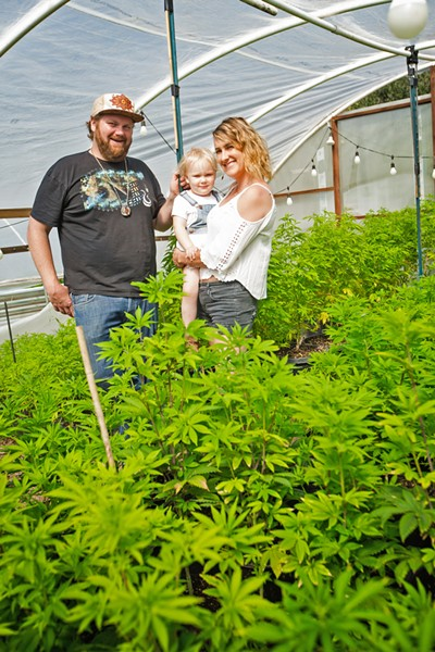 FAMILY FARM Austen Connella (left) and Kristin Kordich (right) pose in front of their Suey Creek cannabis farm with their 3-year-old daughter. - PHOTO BY JAYSON MELLOM