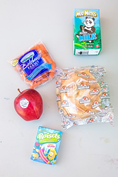 NOT SO STANDARD Participants of the summer meal program can count on not only a snack in their white paper sack but an apple, carrots, a sandwich, and milk. - PHOTO BY JAYSON MELLOM