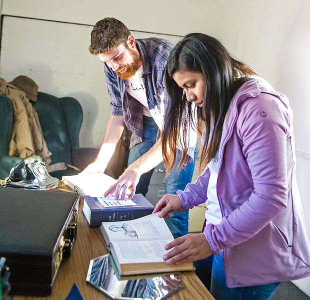 WORKING TOGETHER Escape rooms require team-based problem solving, puzzle cracking, and creative thinking. Pictured, The Lock Boxx owner Will Ruoff (left) and Lauren Marsiglia show how to approach the puzzle for his mobile escape room. - PHOTO BY JAYSON MELLOM