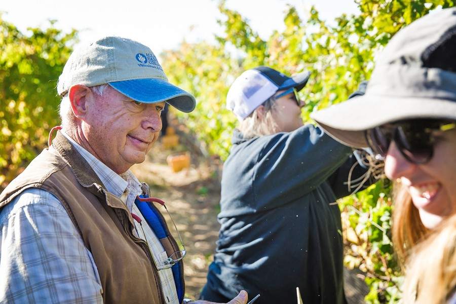 FIELDWORK Ric Fuller (left), head of Allan Hancock College's viticulture operations, takes a break during the Oct. 25 harvest at the Santa Maria campus vineyard. Students work harvests either as volunteers or as part of their viticulture classes. - PHOTO BY JAYSON MELLOM