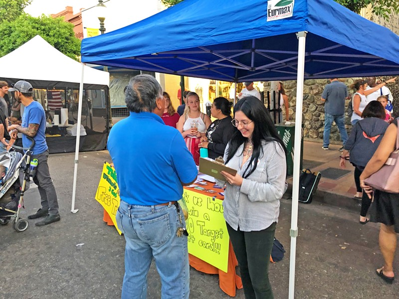 SURVEY TIME One of the Close to Home committee's first steps was to design a survey to try to understand how San Luis Obispo residents view violence in their community. Committee members staff a table at the downtown SLO Farmers' Market. - PHOTO COURTESY OF JANAE SARGENT