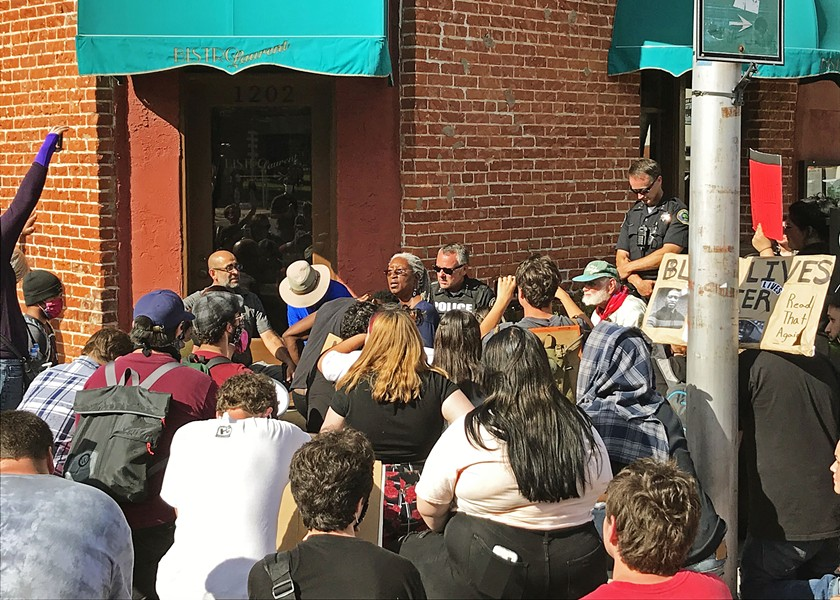 BLACK LIVES MATTER Protesters kneel with police on June 2 in Paso Robles as local business owner Oddette Augustus leads the group in a prayer. The moment marked the end of a six-hour protest against police brutality. - PHOTO BY PETER JOHNSON