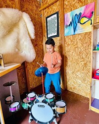 MAKING MUSIC A young Exploration Discovery Center patron makes some tunes in the Music Shed.
