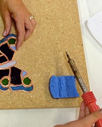 TAKE FLIGHT A class participant at Glasshead Studio makes a mosaic butterfly.
