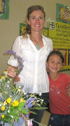 PAGING MRS. GREEN THUMB :  Penny Nyunt posed with her two favorite flowers: wooly blue curls and Lilly (her daughter).