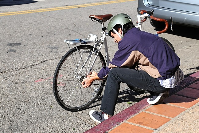 GOLD STATUS:  A Cal Poly student fixes his bike in Downtown SLO. The city was recently elevated from Silver to Gold status as a bike-friendly city by the League of American Bicyclists. The promotion coincides with news that the SLO Police Department received a $190,000 state grant to prevent bike and pedestrian fatalities. - PHOTO BY DYLAN HONEA-BAUMANN