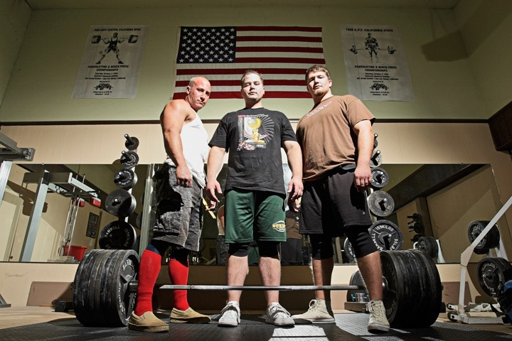 STRONGMEN :  Ian Smalley (left), Alan Best, and George Beckham (right) practice heavy metal magic at Estrada's Gym in SLO; Best stands over a 771-pound bar, his world-record deadlift. - PHOTO BY STEVE E. MILLER