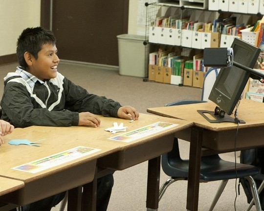 VISION QUEST:  A 12-year-old deaf student uses an up-close reader to help him see his teacher's signing hands. - PHOTO BY STEVE E. MILLER