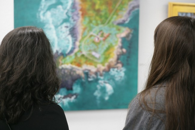 "A COUPLE OF LOOKERS :  Two of the dozens of opening reception attendees soak in Alyce Broome's ""Lighthouse Peninsula,"" a gorgeous aerial view painting. - PHOTOS BY GLEN STARKEY"