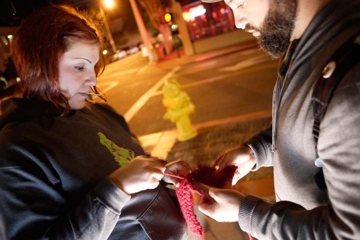 KNIT TAGGERS :  Neal Breton and Adriana Hernandez tag downtown SLO with colorful knitted squares on June 24. - PHOTO BY STEVE E. MILLER