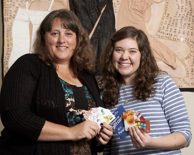 HAPPY HOLIDAYS FOR ALL:  Beth Raub and Anna Clauson (Directors of Volunteers and Outreach) showcase giftcards that have been purchased with donated money for the Women's Shelter of San Luis Obispo. - PHOTO BY STEVE E. MILLER