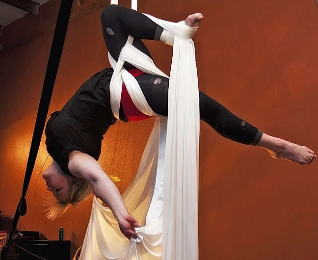 WITH THE GREATEST OF EASE :  Suspended Motion Aerial Arts Academy dancer Liz Stevenson soars through the air on bands of sturdy silk fabric. The local group is currently gearing up for an October performance, and classes are available for kids and adults. - PHOTO COURTESY OF SUSPENDED MOTION