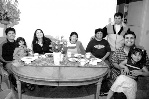 A TABLE TURNED :  The Cerron family, whose house on San Luis Obispos Broad Street burned down in February, gather around their new dining room table, one of several pieces of furniture they received from Claudia Goff. (From left, Efrain Cerron with daughter Rochelle in lap, Betzabeth Cerron, Amanda Cerron, Hector Cerron, Fotunato Cerron (standing), Carlos Erazo, and Jade Cerron, in lap.) - PHOTO BY JESSE ACOSTA