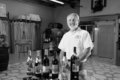 CHECKING THE FLUIDS :  Owner and winemaker Don Peters of Cerro Caliente stands in his winery with a selection of his wines in a tasting room adjacent to his mechanic's garage. - PHOTO BY STEVE E. MILLER