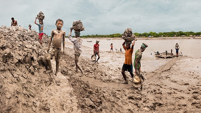 CHANGING WITH THE TIMES:  Workers in Bangladesh build up embankments and make the river bed lower in response to climate change raising sea levels in the digital composite image 'Building Up The Embankment Along The Kholpetua River' by Carrie and Eric Tomberlin. On average, images in the couple's series on climate change are a product of about 70 different photos fused together to give the viewer a broader understanding. - PHOTO COURTESY OF CARRIE AND ERIC TOMBERLIN