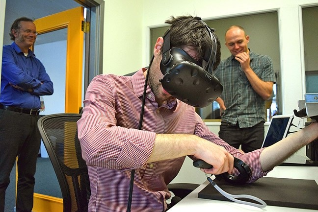 NEW TECH:  AxonVR founder Jake Rubin hitches a virtual ride through reality in a demonstration of one of his company's products. - PHOTO BY OLIVIA DOTY