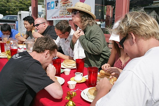 READY? GO! :  The dozen or so contestants rip into plates of pancakes, except for Effie (standing), who makes a show of taking her sweet time because she's just here for a free lunch. - PHOTO BY GLEN STARKEY