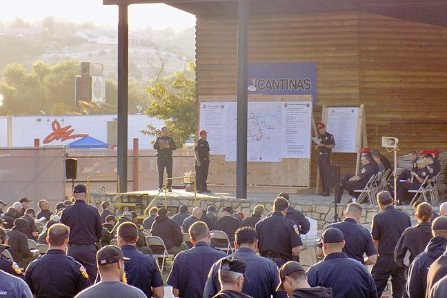 FIRE SEASON:  Hundreds of firefighters attend an Aug. 17 Chimney Fire briefing at the Paso Robles Mid-State Fairgrounds. The fire has burned 7,300 acres south of Lake Nacimiento with 25 percent containment as of press time. - PHOTO BY PETER JOHNSON