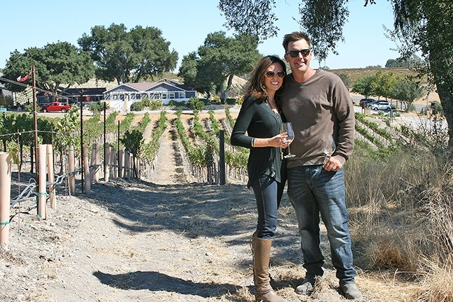 BETTER TOGETHER:  Joe and Jenny Barton enjoy a glass of wine in their estate vineyard, which overlooks the 80-year-old Barton Family home. - PHOTO BY HAYLEY THOMAS CAIN