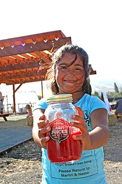 PHOTO BY HAYLEY THOMAS CAIN - FIELD DAY Six-year-old Giuliana Dorado of Julia's Juices celebrates harvest at a rare public City Farm SLO event earlier this month. Behind her, a recently completed pergola offers wind protection for events to come.