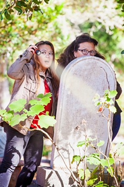 PHOTO COURTESY OF PAULA MCCAMBRIDGE - BEHIND THE SCENES Elaine Chaney (left) and Paula McCambridge, the voices behind Wait, Whaaat?, pose in a graveyard, a fitting place for their humorous, conspiracy theory podcast.