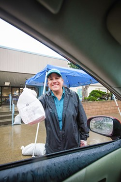 PHOTO BY JAYSON MELLOM - FREE AND REDUCED Cynthia Van Gerwen hands out free lunches at Baywood Elementary School in Los Osos on March 16. Schools are closed in an effort to prevent the spread of the novel coronavirus, but school districts are still providing free meals to kids.