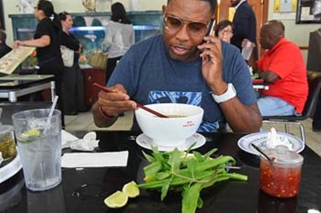 Malik Shakur enjoys his lunch at Pho Lein Hoa, while on the phone.  mh