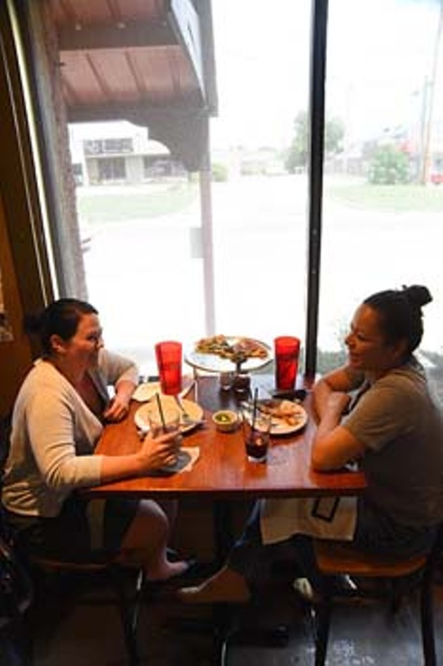 2 women enjoy their pizza by the window watching Western Avenue go by, recently at The Wedge.  mh